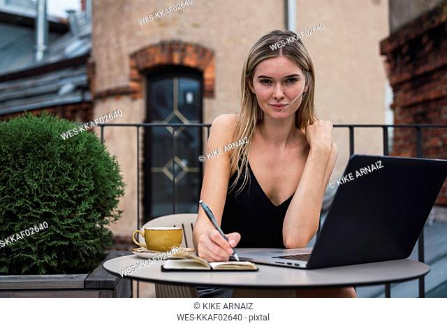 Portrait of young woman sitting on balcony with laptop taking notes