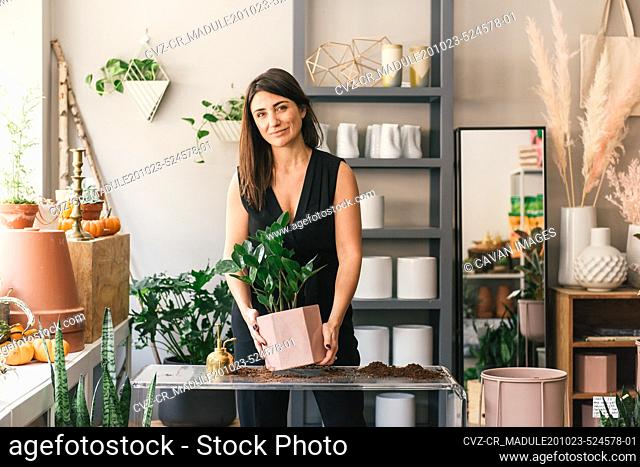 Florist looking to camera in testimonial while potting plant