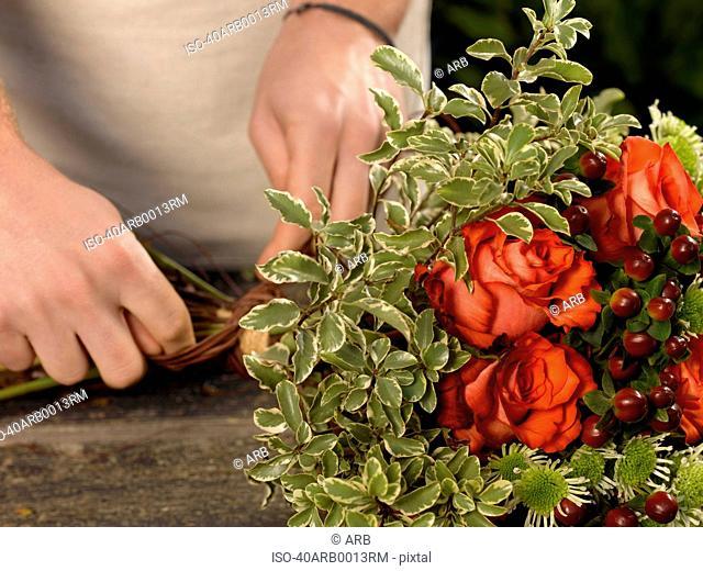 Florist tying bouquet in shop