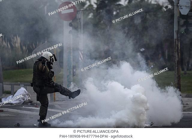 08.09.2018, Greece, Thessaloniki: A policeman steps against a tear gas cartridge during a demonstration against the agreement between Greece and Macedonia...