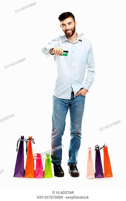 Handsome man with shopping bags and holding credit card. Christmas and holidays concept
