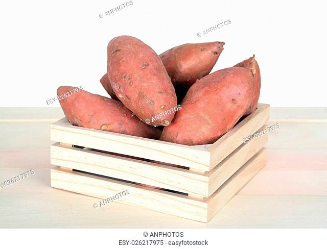 fresh sweet potatoes on table against white background