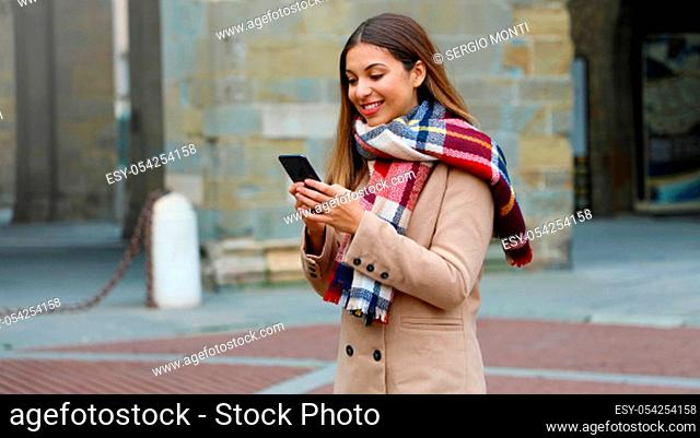 Happy smiling woman with coat and scarf using smart phone outdoor in city street