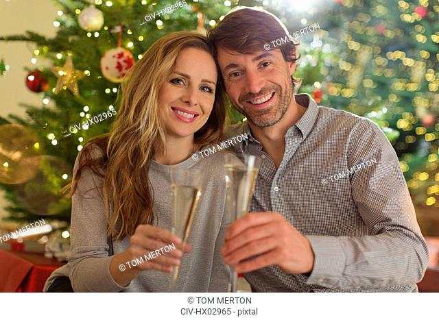Portrait smiling couple toasting champagne flutes in front of Christmas tree