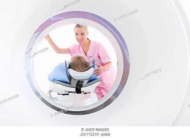 Technician nurse preparing patient at CT scanner tube in hospital