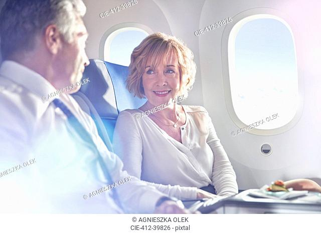 Businessman and businesswoman talking in first class on airplane