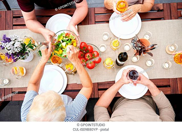 Overhead view of family handing salads at family lunch on patio