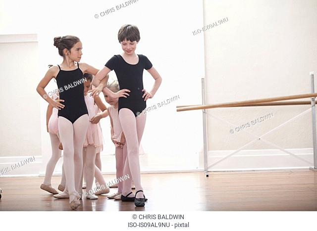 Group of girls practicing with hands on hips in ballet school