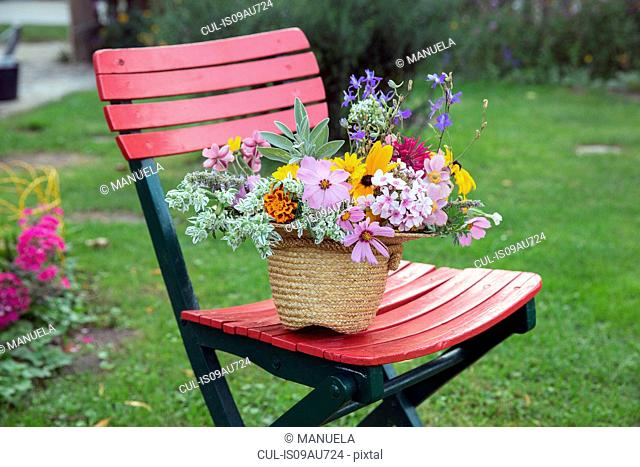 Fresh cut flowers in straw hat, on garden chair