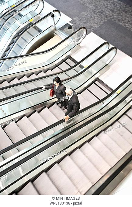 Mixed race pair of business people on the way to a meeting near a set of escalators