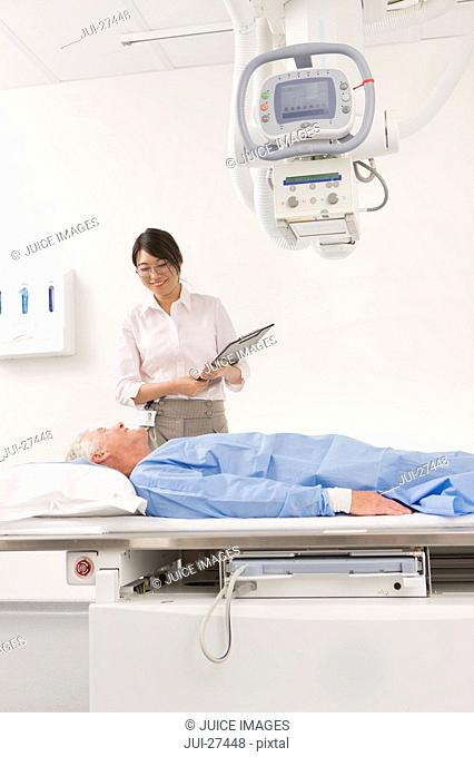 Radiologist helping patient with x-ray machine