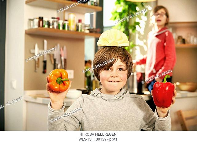 Portrait of smiling boy standing in kitchen with half of white cabbage on his head and bell peppers in hands