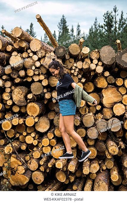 Happy young woman balancing on stack of wood