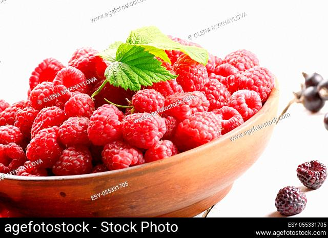 Ceramic bowl with organic raspberries on white table