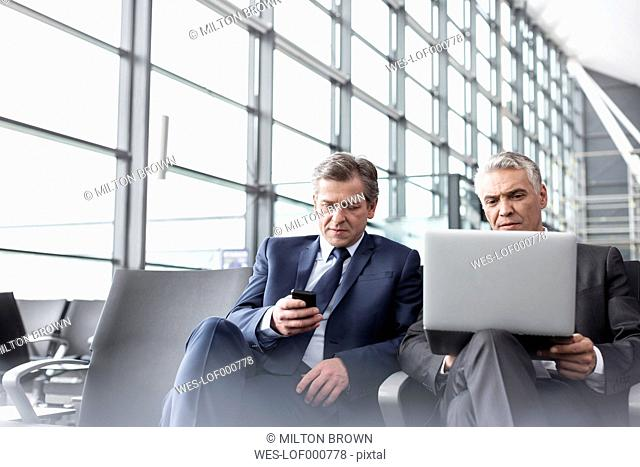 Two businessmen with cell phone and laptop at airport departure lounge