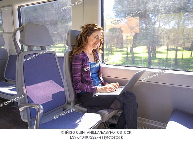 brown hair smiling woman dressed in purple and blue, sitting traveling by train typing in keyword of laptop computer leaning on her legs