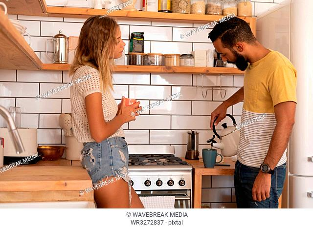 Couple talking with each other at home in kitchen room