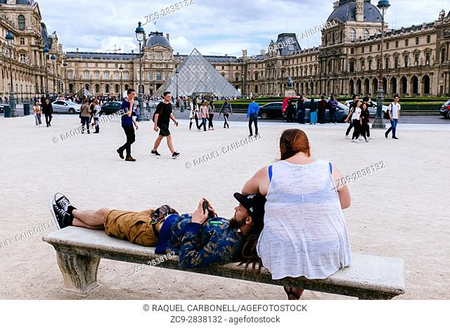 Couple playing with mobile phone on a stone bench in Place du Carrousel in front of Louvre museum pyramid. Paris, Île-de-France, France