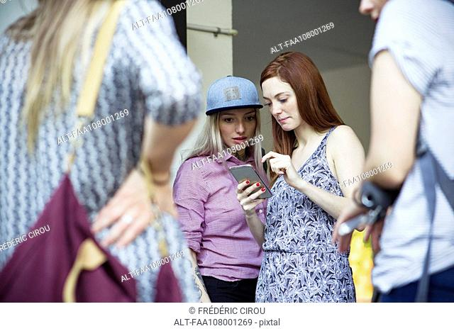 Female friends looking at smartphone together