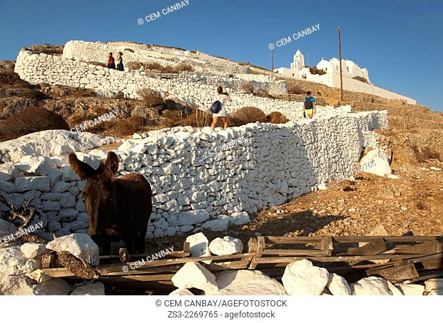 People walking up to the Panagia Kimissis church situated at the cliff in Hora, Folegandros, Cyclades Islands, Greek Islands, Greece, Europe