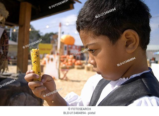 Young boy with baby corn