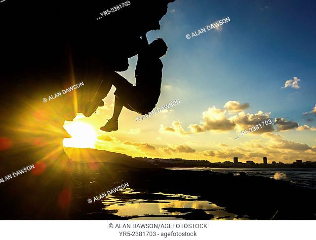 Climber on volcanic coastal boulder at sunrise at El Confital, Las Palmas, Gran Canaria, Canary Islands, Spain