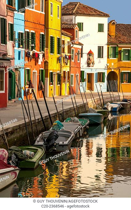 Colored houses facades along a canal , Burano island, Venice, Italy