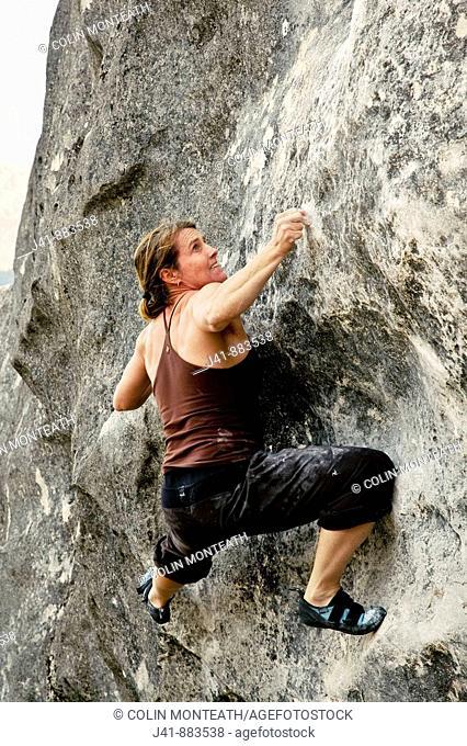 Rock climber on 'Millennium' , boulder at Flock Hill, Canterbury, New Zealand