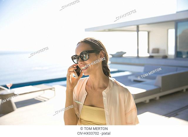 Smiling woman talking on smart phone on sunny modern, luxury home showcase exterior patio