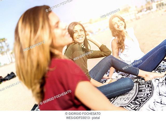 Three happy female friends sitting on the beach