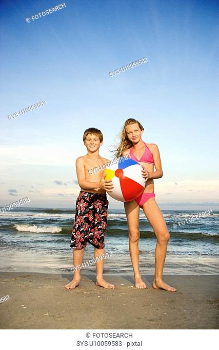 Caucasian pre-teen boy and girl holding beach ball on beach