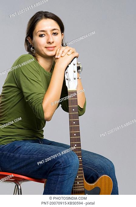 Portrait of a young woman holding a guitar