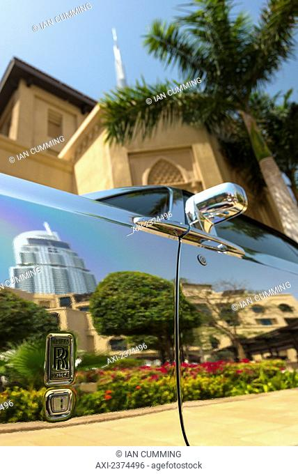 Detail of chrome plated Rolls Royce beneath palm tree and traditional arabic style hotel with the Burj Khalifa behind; Dubai, United Arab Emirates