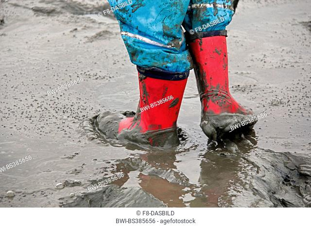 child walking through the mud flat, waterproof pants and rubber boots, Germany, Lower Saxony, Cuxhaven