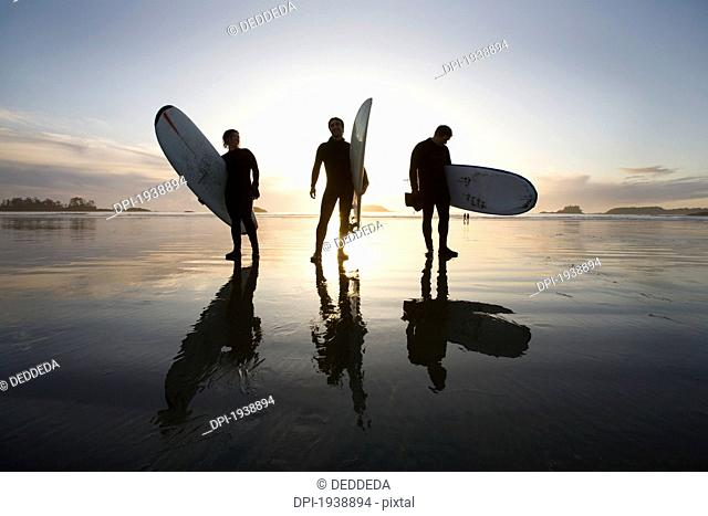 silhouette of three surfers carrying surfboards, chesterman beach tofino vancouver island british columbia canada