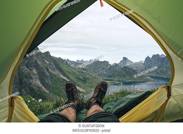Norway, Lofoten, Moskenesoy, Feet of man, lying in a tent over Kjerkefjord