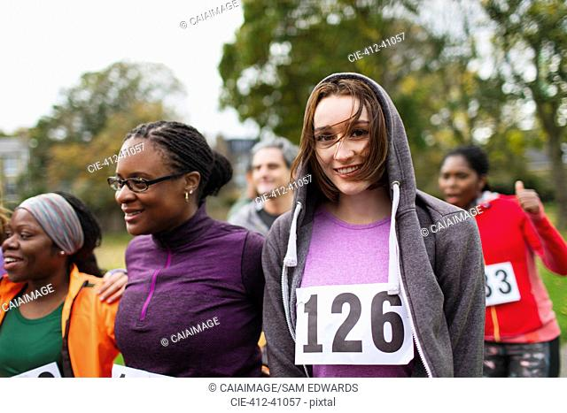 Portrait smiling female runner at charity run in park