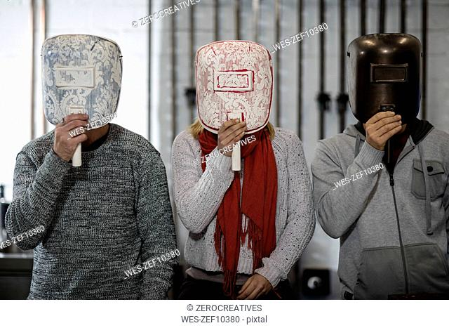 Three people hiding behind designer masks