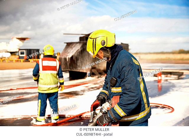 Firemen training, firemen checking fire hose after mock helicopter fire at training facility