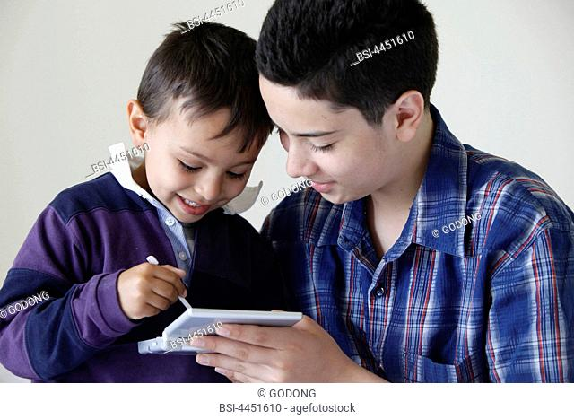 Brothers playing an electronic game