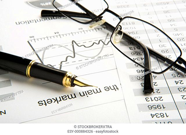 Close-up of fountain pen, eyeglasses and financial documents