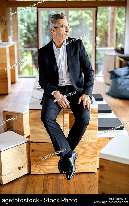 Mature businessman looking away while sitting on table at home