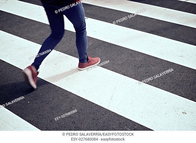 Young woman crossing a zebra crossing. Zaragoza, Aragon, Spain