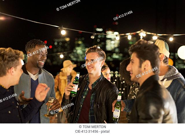 Young men drinking beer and talking at rooftop party
