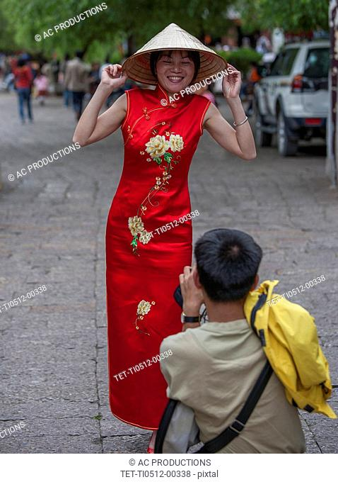 Man photographing woman wearing red dress in Lijang, Shangri-La Region, Yunnan Province, China