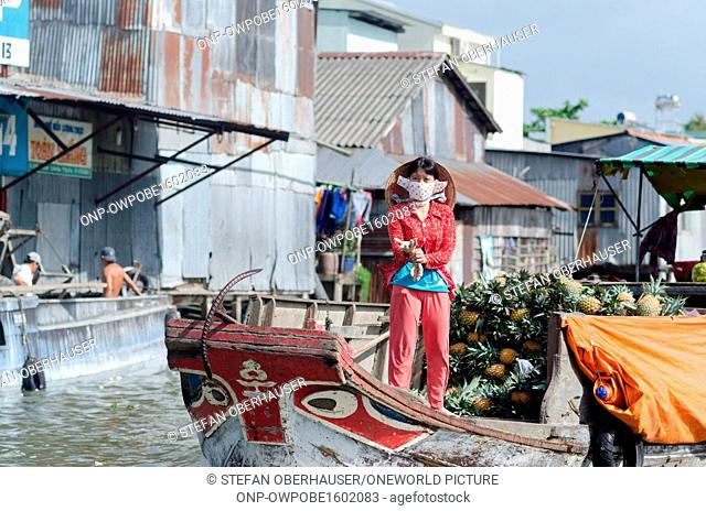 Vietnam, Can Tho, market woman on a boat loaded with pineapples in the Mekong Delta