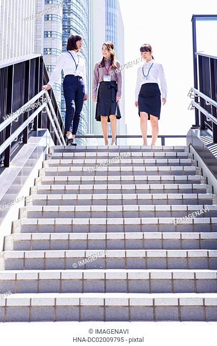 Business women going down the stairs at downtown area
