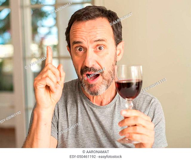 Middle age man drinking a glass of wine surprised with an idea or question pointing finger with happy face, number one
