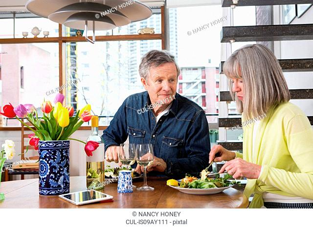 Couple enjoying meal at dining table