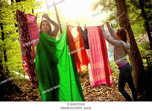 Girls hanging laundry on clothesline in forest
